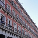 Travelling for fun, things to do in Madrid, visit Spain: A man looks over his balcony on Plaza Mayor. What a spot to live!