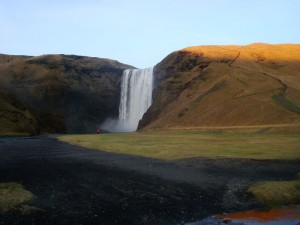 Travelling for fun, Skogafoss Waterfall, Things to do in Iceland and Reykjavik: A person dwarfed by Skogafoss Waterfall
