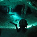 Travelling for fun, visit Mexico, Yucatan, Cenote: A diver lights the stalagtites ahead inside in the tunnel in Dos Ojos