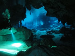 Travelling for fun, visit Mexico, Cenote: A diver with a lamp emerging from the tunnels back to the bright surface pool full of swimmers