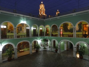 Travel for fun, Mexico, Yucatan Peninsula - what to do in Cancun to Merida,, Merida : The orange lights of the cathedral peek up in the background of the square of the governments palace in Merida. The murals that adorn the walls represent the conflict between the Mayans and the Spanish.