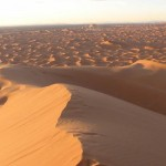 Visit Morocco, things to do in Merzouga, Erg Chebbi, Sahara Desert, Travelling for Fun: A panoramic view at sunset from the top of the highest dune in Erg Chebbi outside Merzouga. The colours of the desert are changing by the minute.